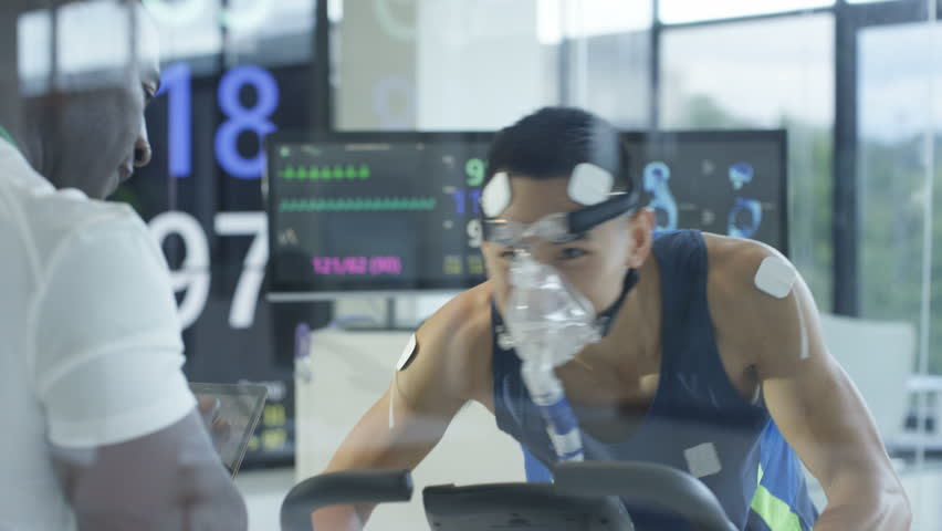 4K Male athlete on exercise bike being tested & monitored by sports scientist Dec 2016-UK