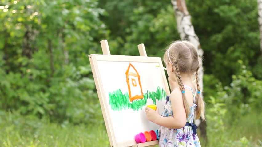 Little girl painting a dream home in the park