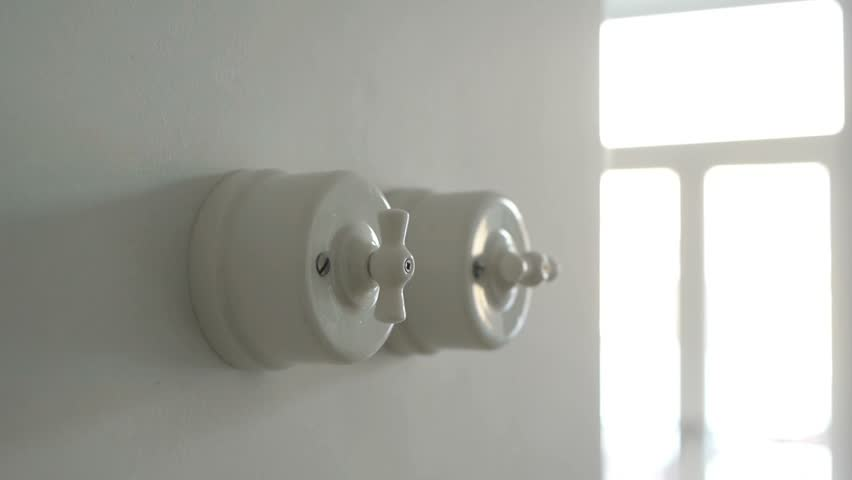 A Man Hand Turning On And Off White Ceramic Vintage Light Switch In