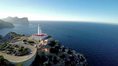 Aerial view of a lighthouse named Faro de Formentor, located in Cap de Formentor on the top of a cliff in the island of Majorca, with a beautiful sunset.