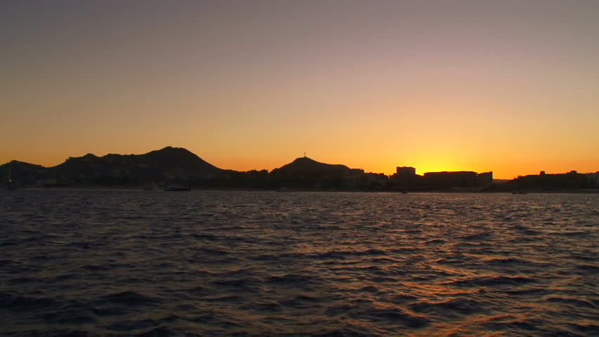 Sunset over Cabo San Lucas, Mexico and ocean water from boat.
