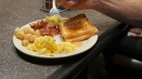 A dolly shot of a man eating a really good continental breakfast at a hotel with bacon, eggs, hashbrowns and french toast