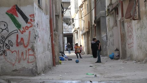 RAMALLAH, WEST BANK - OCTOBER 2016: Kids play football (soccer) in the narrow alleys of the permanent Palestinian refugee camp (Al Amari) in Ramallah in the West Bank