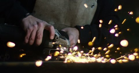 .blacksmith or welder,with its grinding smooths steel and iron,in extreme slow motion,to make the surface smooth.The grinding wheel contact with the iron causes sparks.concept:work,locksmith industry.