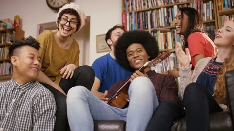 4K Happy young friends in shared apartment playing guitar & socializing Dec 2016-UK
