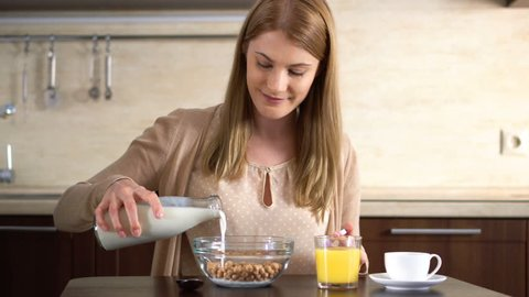Beautiful young attractive woman pouring milk into a bowl of cornflakes in the kitchen.