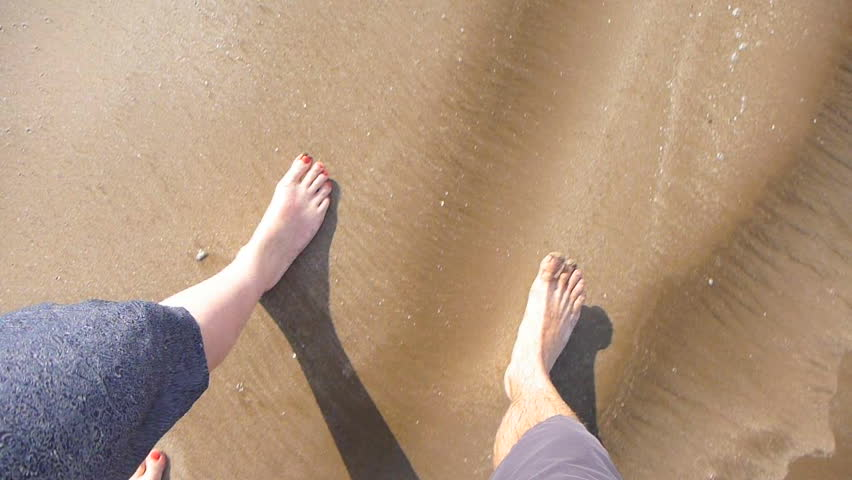 Man and woman's feet point of view while walking on sandy beach with waves crashing.