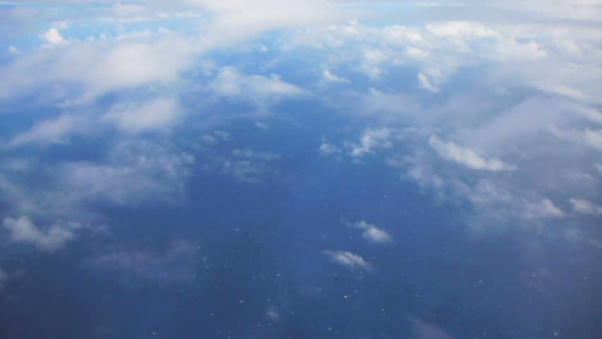 Flying in airplane over Pacific ocean dropping in altitude flying through clouds and little turbulence.