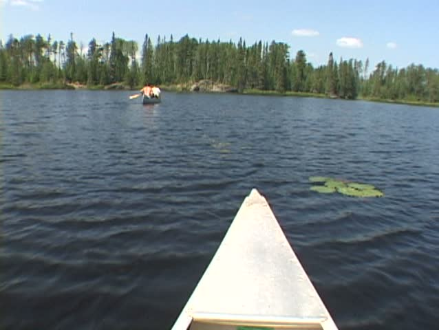 Point of view while riding inside aluminum canoe at lake in the Minnesota Boundary Waters following two people in canoe. More clips available in series.