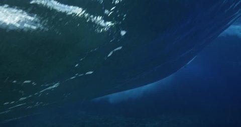 Underwater view of surfer riding ocean wave