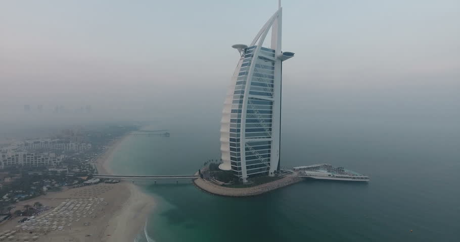 DUBAI, UAE - JANUARY 4, 2017:Aerial view of Burj al Arab hotel at sunrise.The Burj al-Arab is a symbol of Dubai and a luxury hotel standing on an artificial island next to Jumeirah beach.foggy weather