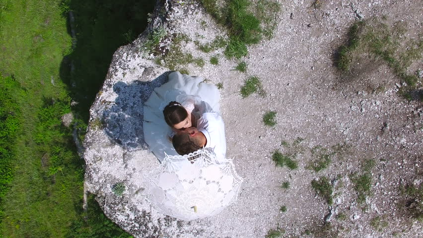Aerial view of couple of newlyweds standing on a cliff kissing | Shutterstock HD Video #23113240