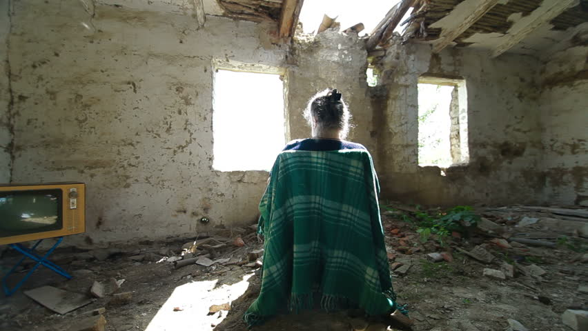 DOLLY: Lonely Old Age. Senior woman looking out the window abandoned house.
