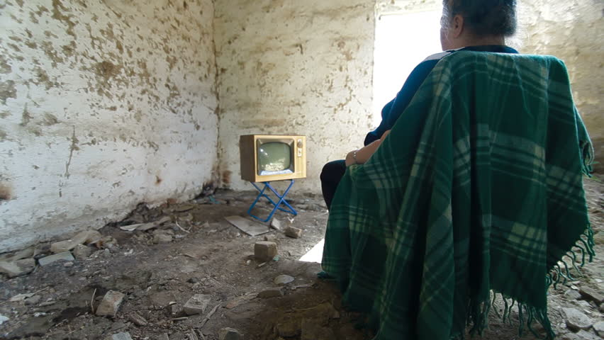 Senior Woman Watching Old TV In An Abandoned House, Dolly Shot, Rear View