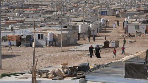 ZAATARI REFUGEE CAMP, JORDAN - 18 NOVEMBER 2016: Syrian refugees walk through makeshift homes in the Zaatari camp in Jordan