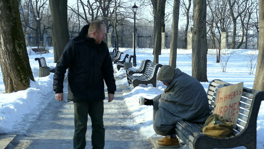 Passer giving alms for young homeless man.  Sign on cardboard - I'm homeless,  help me! | Shutterstock HD Video #23157400