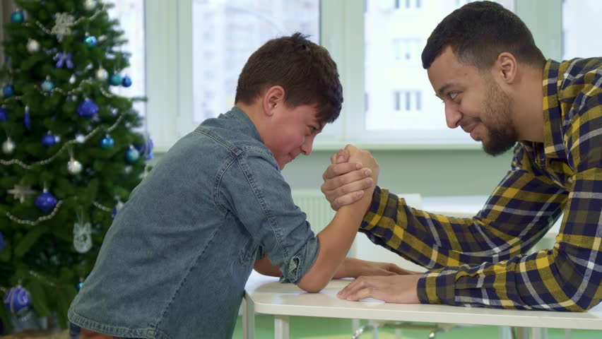 Attractive father and son armwrestling on the table. Little boy defeating his parent against background of christmas tree. Handsome african american man succumbing to his kid