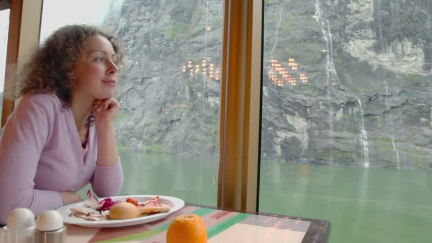 Woman sits at table with food and watch waterfall on mountain at coastline of fjord outside window