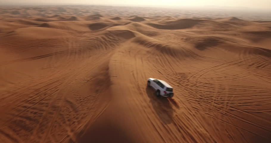 Aerial view of 4x4 off road land vehicle taking tourists on desert dune bashing safari in Dubai, UAE