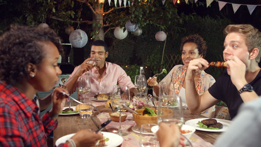Young Adult Friends Eat And Drink At An Outdoor Dinner Party