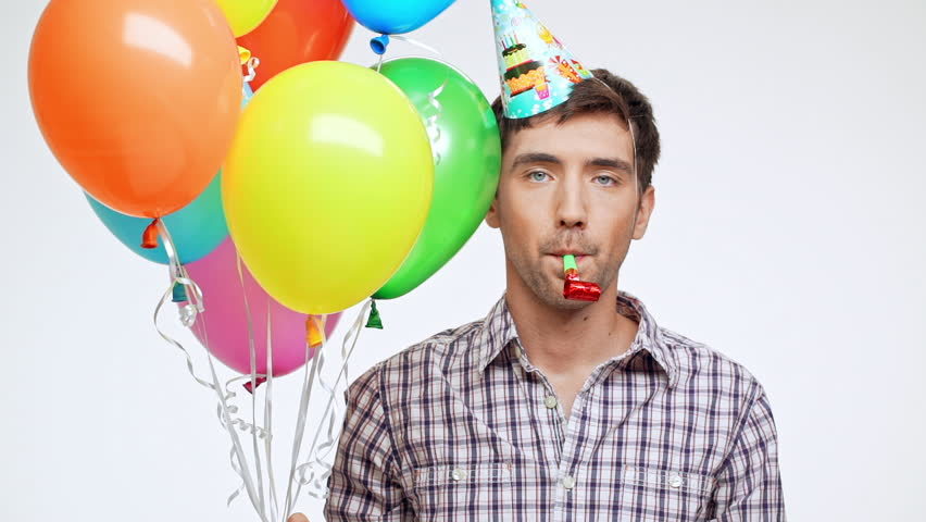 Young Caucasian male with dark hair and light bristle on white background wearing birthday cap sadly releases multicolored balloons in slowmotion