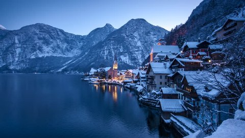 Day to night time-lapse footage of famous historic Hallstatt lakeside town embedded in beautiful winter wonderland scenery in the Alps during scenic Christmas time, region of Salzkammergut, Austria