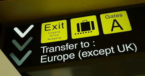 Detail of Airport sign with instruction direction toward Exit (Uitgang, Sortie, Ausagang), luggage claim, gates A and text Transfer to Europe with exception of the UK (Brexit concept)