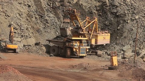 a large excavator working in a quarry, ship ore to the big yellow truck, iron ore mine, iron ore, big yellow mining truck at worksite, big truck, mining truck, extraction, mining, quarrying