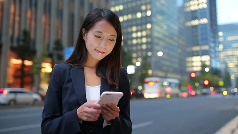 Businesswoman touching on cellphone at street