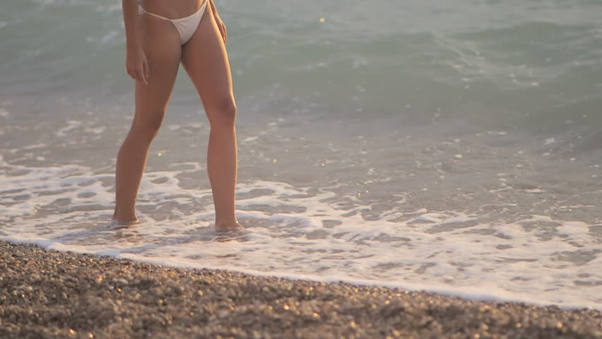 Young beautiful sexy woman in a bikini with blond hair is on the shore of the sea on the beach at sunset. She smiled enigmatically, stroking himself and looks seductively at the camera. Slow motion | Shutterstock HD Video #23320540