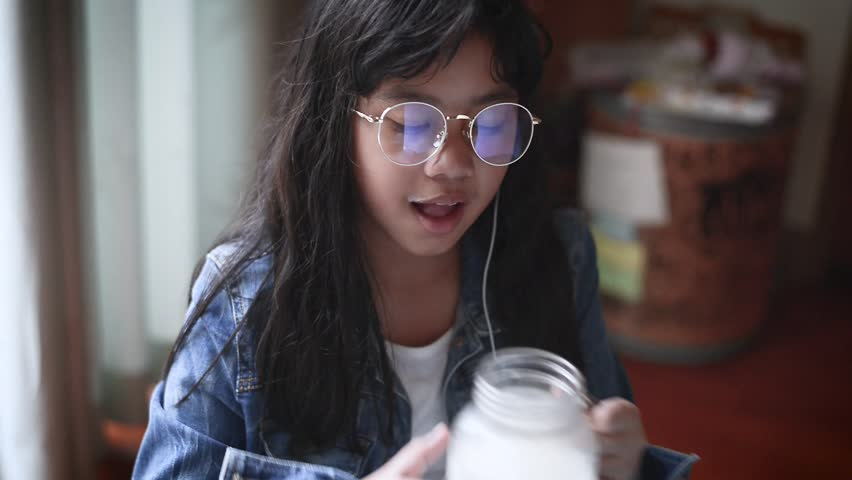 Portrait of smiling girl  listening to music and drinking milk in the living room  . Milk mustache  | Shutterstock HD Video #23325100