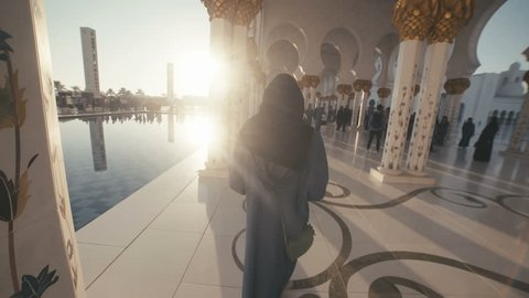 UAE, 2017: Sheikh zayed grand mosque. Mosque in Abu Dhabi. A young woman of European appearance in the traditional dress of Muslim women - black Abai - walking inside the mosque.