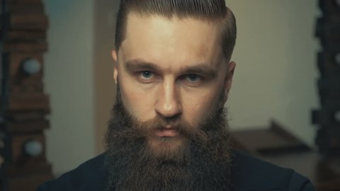 Portrait of handsome serious unshaven guy with long beard