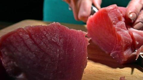 Woman cutting tuna fillet. 4K close-up dolly shot