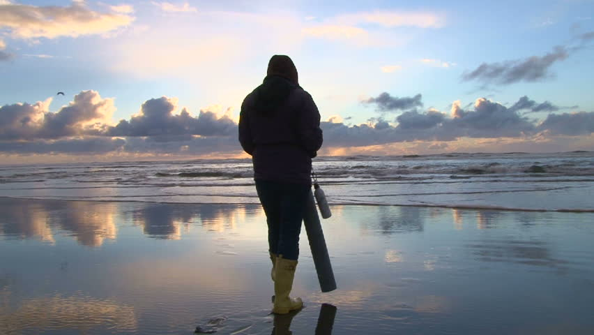 Woman with clamming gun walks Pacific Ocean in search for razor clams.