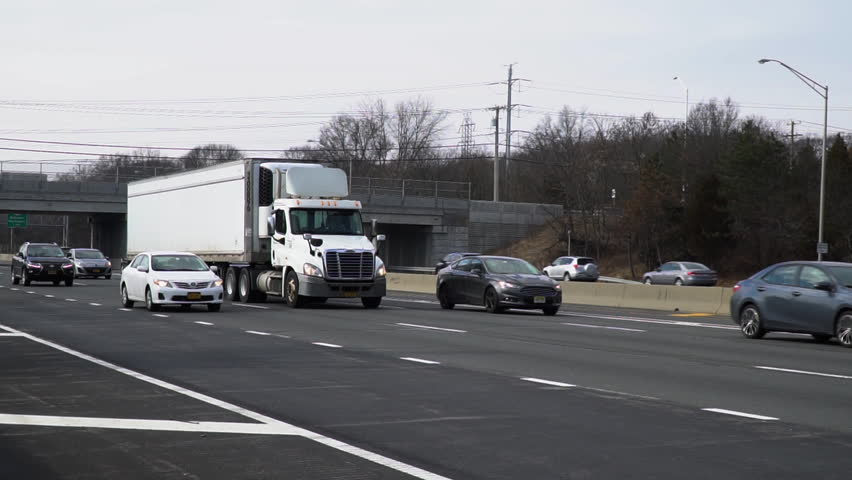 Large Semi Tractor Trailer Rig Traveling On Long Island Expressway In Slow Motion Towards New York City Cargo Container Vehicle Transport Materials