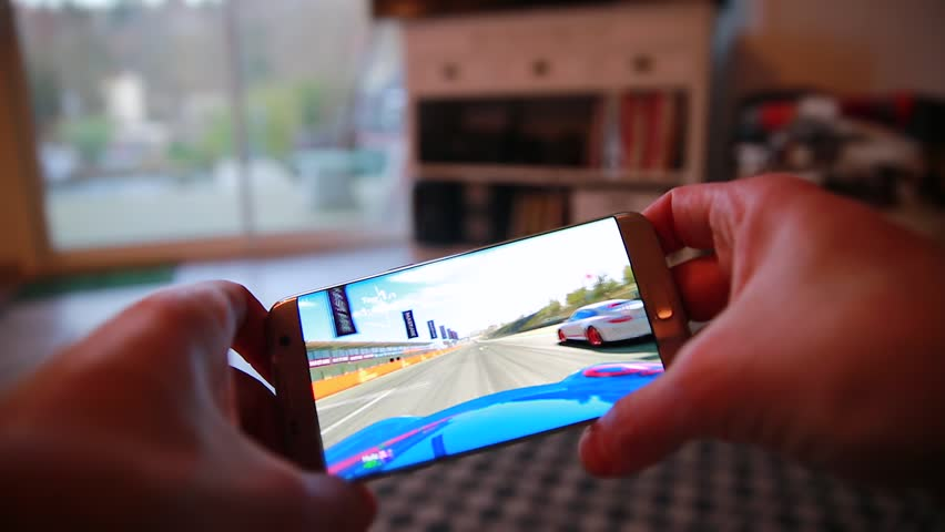 Paris, France, January 25, 2017: Man Playing Real Racing 3 (EA Games) Video Game On His Modern Smartphone Samsung Galaxy S7 Edge At Home