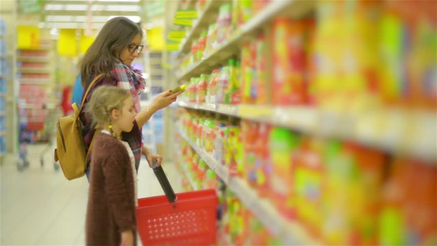 Young Mom and Child Buying Food in a Supermarket. Beautiful Woman with Cute Girl Standing Near Shelf With Goods Looks Carefully on Every Products | Shutterstock HD Video #23415844