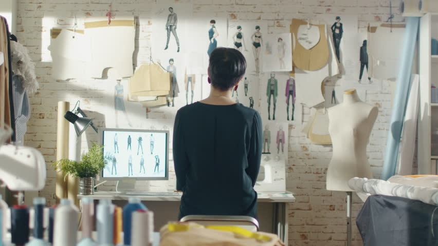 Zoom Out of a Female Fashion Designer Looking at Drawings and Sketches that are Pinned to the Wall Behind Her Desk. Studio is Sunny. Personal Computer, Colorful Fabrics, Sewing Items are Visible. | Shutterstock HD Video #23430100