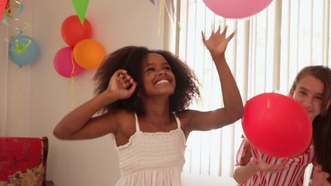 Group of happy children celebrating birthday at home, kids and friends having fun at party. Portrait of beautiful black girl smiling at camera and playing with balloons. Slow motion