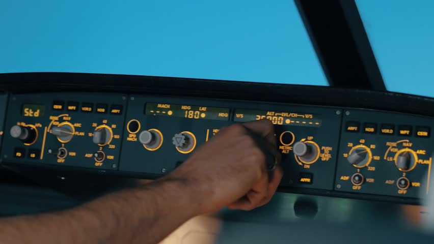 Close shot of glareshield in  cockpit - front panel of modern aircraft with first pilot turning knob on flight deck with lights.