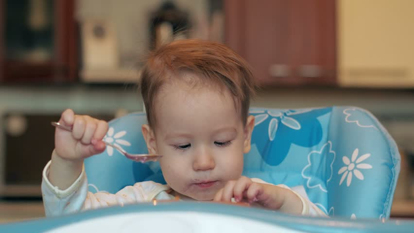Young mom wipes her baby's mouth and face with napkin after taking food. He put his hands into dirty plate and begin to cry loudly