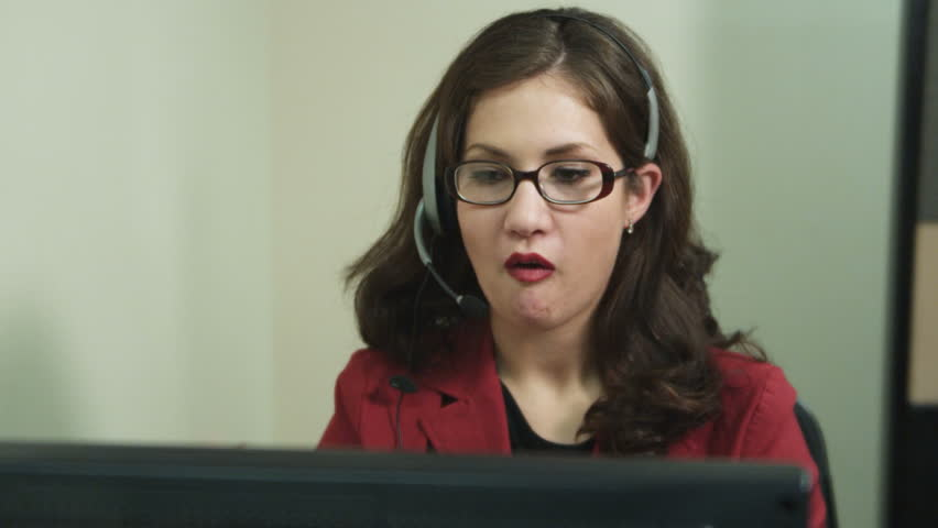 office worker types on a computer and chews gum