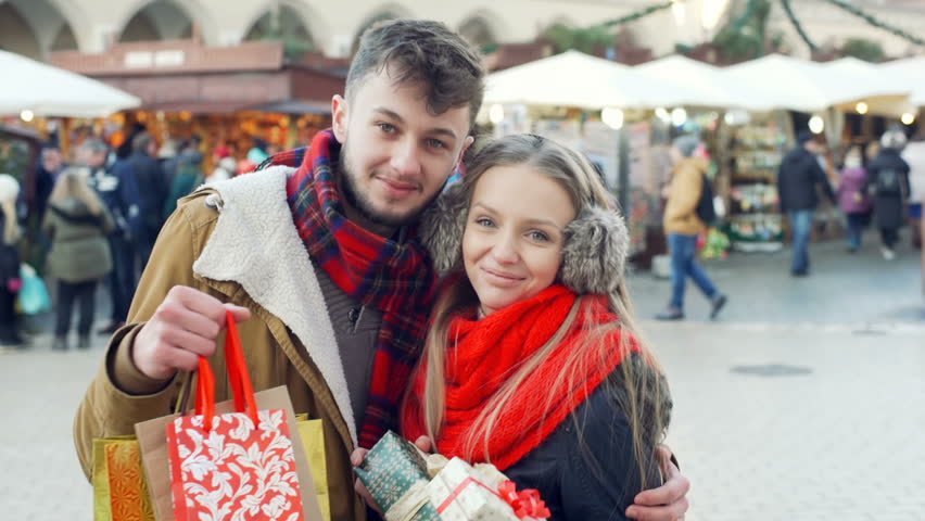Lovely couple holding christmas presents and smiling to the camera, steadycam shot  | Shutterstock HD Video #23456470