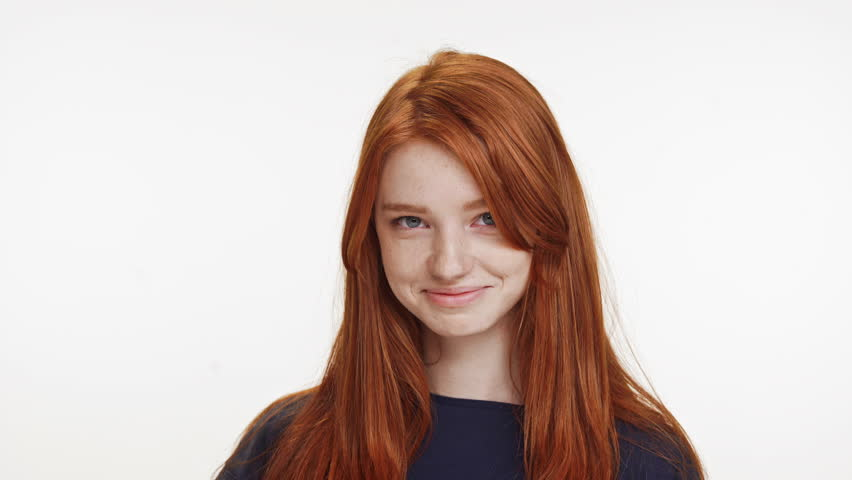 Shy coy ginger Caucasian teenage girl standing smiling on white background