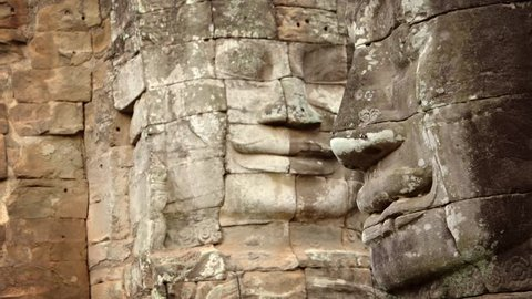 Enormous and ancient. hand-carved stone faces. encrusted with lichen and smiling eternally. at Bayon Temple Ruin in Cambodia.