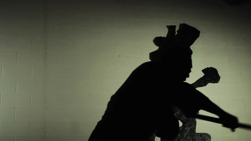 A Shaolin monk demonstrates in silhouette an ancient form of kung fu using a staff. Shot in slow motion.