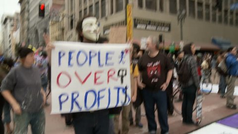 "Occupy Protester 'Vendetta' Mask. Protester wears a 'vendetta' mask and holds a sign that reads: ""PEOPLE OVER PROFITS"" at an Occupy Rally in downtown Los Angeles, California on May 1st, 2012."