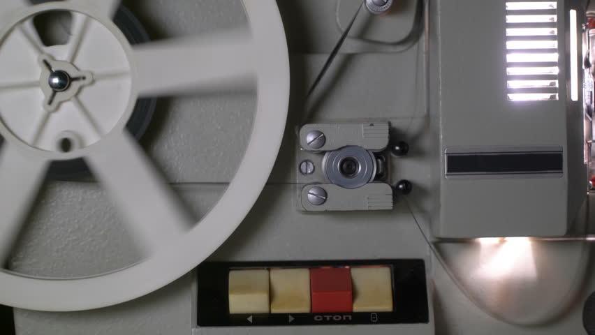 Vintage 8 mm movie projector film reel revolves close up. Concept of old cinema