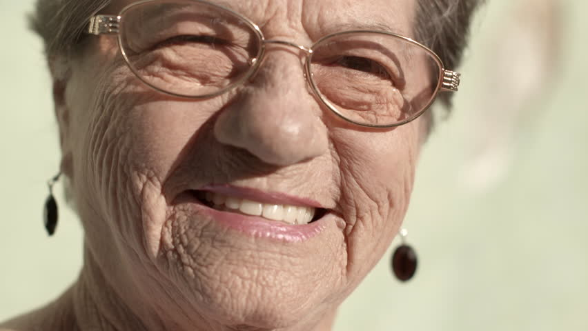Senior portrait of old caucasian woman with eyeglasses looking at camera and smiling. Closeup